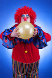 Clown with a ballon in hands on blue background Stock Photography