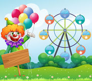 A clown with balloons at the back of an empty board Royalty Free Stock Photos