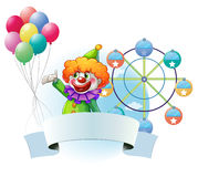 A clown with balloons, an empty banner and a ferris wheel at the Royalty Free Stock Photos