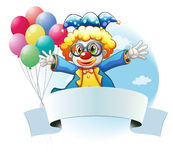 A clown with balloons and the empty signage Royalty Free Stock Photo