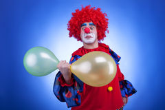 Clown with balloons in hand on blue background Royalty Free Stock Images