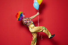 Clown with balloons on red background Royalty Free Stock Images