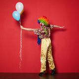 Clown with balloons on red background Stock Images