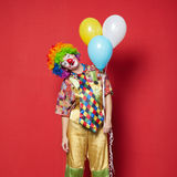 Clown with balloons on red background Stock Image