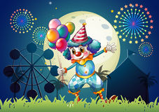 A clown with balloons standing in front of the carnival. Illustration of a clown with balloons standing in front of the carnival Royalty Free Stock Image