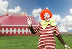 Clown with big bow tie over circus tent background Stock Photo