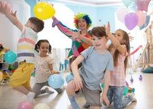 Clown bij de partij van de kinderenverjaardag het onderhouden jonge geitjes royalty-vrije stock foto's