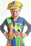 Clown boy with arms akimbo and painted face. Small boy with arms akimbo, red painted face and angry expression Stock Photo