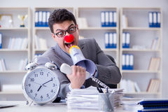 The clown businessman angry in the office with a megaphone. Clown businessman angry in the office with a megaphone Stock Image
