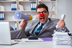 The clown businessman angry in the office with a megaphone. Clown businessman angry in the office with a megaphone Stock Photography