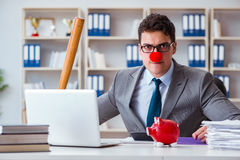 The clown businessman with a baseball bat and a piggy bank Stock Photography
