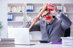 The clown businessman with a baseball bat and a piggy bank Stock Photo