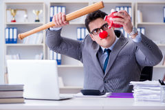 The clown businessman with a baseball bat and a piggy bank Stock Image