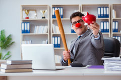 The clown businessman with a baseball bat and a piggy bank Stock Images