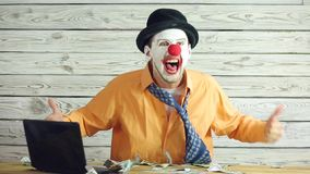 Clown businessman and money. Clown businessman dancing with money. Clown throws money and puts it in his pockets. Concept of businessman idiot stock video footage