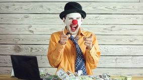 Clown businessman and money. Clown businessman dancing with money. Clown throws money and puts it in his pockets. Concept of businessman idiot stock video