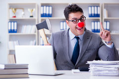 The clown businessman  in the office with an axe. Clown businessman  in the office with an axe Royalty Free Stock Photography