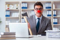 The clown businessman  in the office with an axe. Clown businessman  in the office with an axe Royalty Free Stock Image
