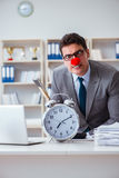 The clown businessman in the office with an axe and an alarm clock Royalty Free Stock Image