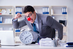 The clown businessman in the office with an axe and an alarm clock Stock Image