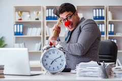 The clown businessman in the office with an axe and an alarm clock Royalty Free Stock Photos