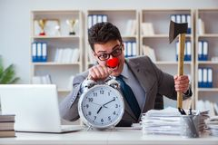The clown businessman in the office with an axe and an alarm clock royalty free stock images