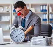 Clown businessman in the office with baseball bat and an alarm c