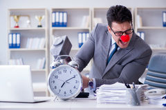 The clown businessman in the office with hammer and an alarm clock Stock Image