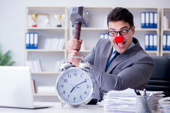 The clown businessman in the office with hammer and an alarm clock Stock Photos