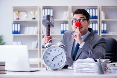 The clown businessman in the office with hammer and an alarm clock Stock Photo