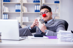 The clown businessman in the office with the a money sack Royalty Free Stock Photo