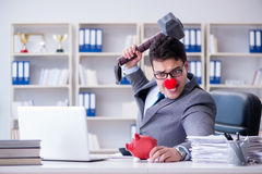 The clown businessman with a piggy bank and a hammer Stock Images