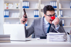 Clown businessman working in the office angry frustrated with a. Gun Stock Photos