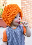Clown child eating lollipop in a party Royalty Free Stock Photos