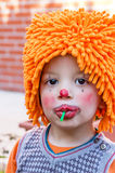 Clown child eating lollipop in a party Royalty Free Stock Photo