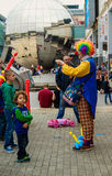 Clown with children's. Bristol, UK - July 16, 2016: A clown selling the balloons in The Harbour Festival in Bristol, UK Royalty Free Stock Image