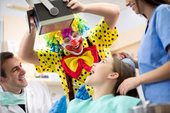 Clown in colorful clown suit make laugh young girl in dental amb Stock Image
