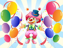 A clown with a colorful costume surrounded by balloons Royalty Free Stock Photo