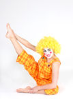Clown in colourful costume doing gymnastic Stock Photo
