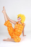 Clown in colourful costume doing gymnastic Stock Image