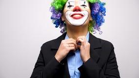 Clown con una parrucca e un vestito che chiudono il bottone dalla camicia archivi video