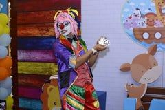 Clown in costume viola che fa la magia del ` s dei bambini immagine stock libera da diritti