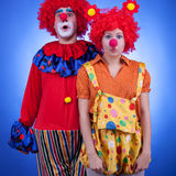 Clown couple in costumes on blue background Royalty Free Stock Images