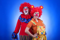 Clown couple in costumes on blue background Royalty Free Stock Photo