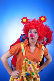 Clown couple in costumes on blue background Stock Image