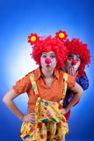 Clown couple in costumes on blue background Royalty Free Stock Photos