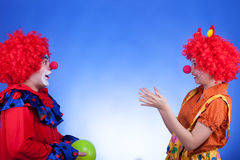 Clown couple playing with ballon on blue background Royalty Free Stock Images