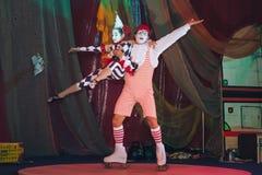 Clown dans un T-shirt rayé et des rouleaux sur ses pieds, tenant une petite fille sous forme de harlequin, bras tendus dans la sa images libres de droits