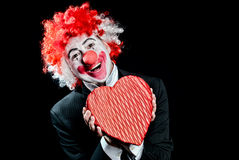 Clown Date love. Colorful clown with a box of candy  on a black background Stock Photos