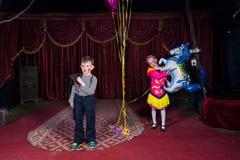 Clown de garçon sur l'étape avec la fille tenant le ballon de cheval Photographie stock